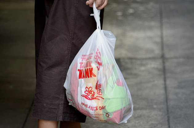 A man holding a plastic bag with items inside.