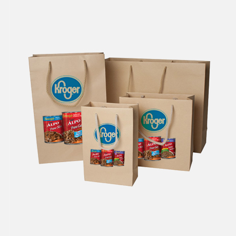Four different sized brown paper bags with handles printed with a brand name and product images in front.