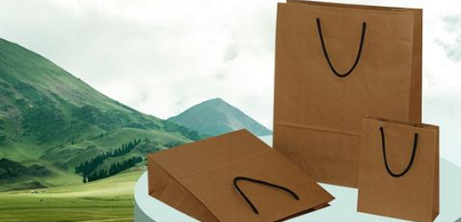 Three paper shopping bags with handles placed on the table with green mountains on the background.