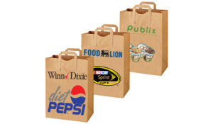 Three brown paper bags with handles printed with different brand names and logos in front.