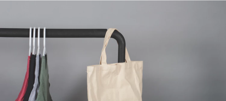 A reusable bag hanged at the corner with four clothes hanged in the center.
