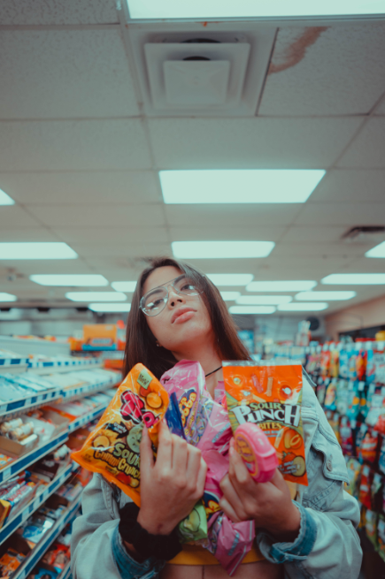 A girl wearing an eyeglass in a grocery store, holding different kinds of candy in a plastic bag.