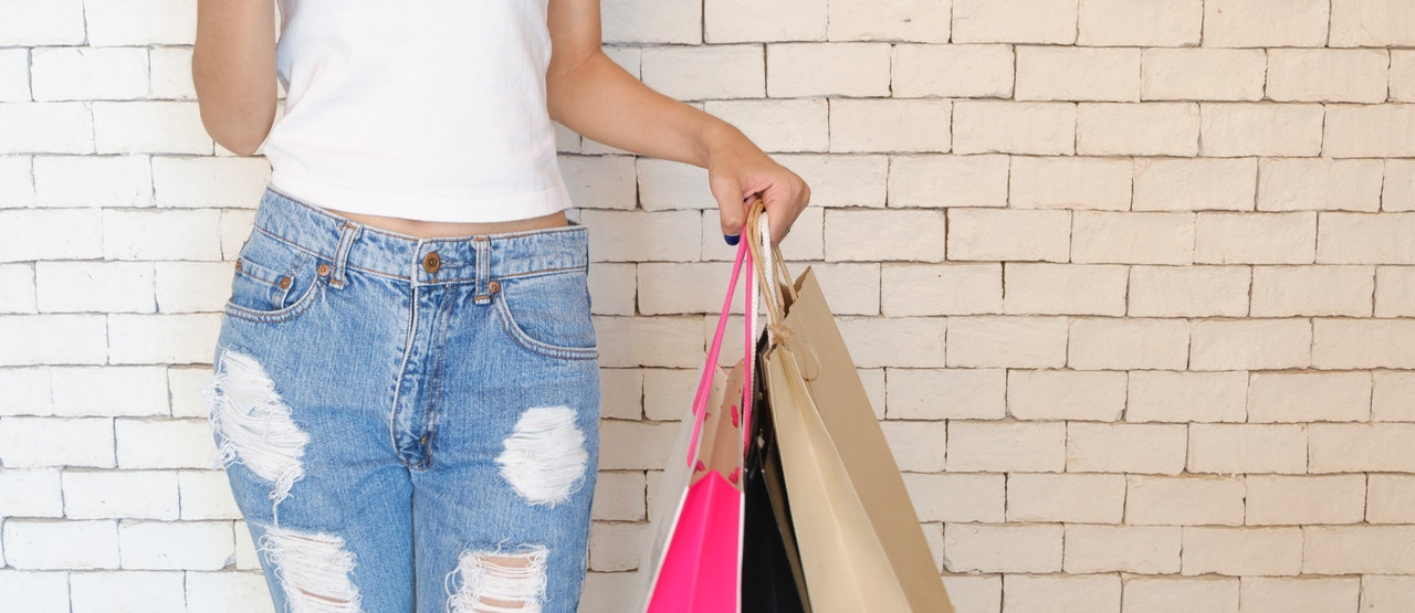 A woman in white shirt and ripped jeans standing and holding three paper bags.