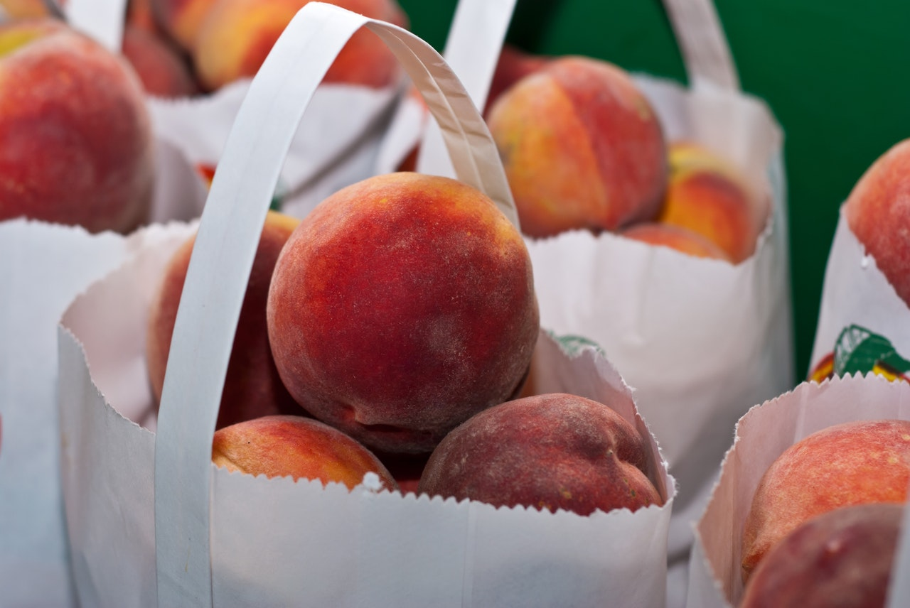 White paper bags with fruits inside.