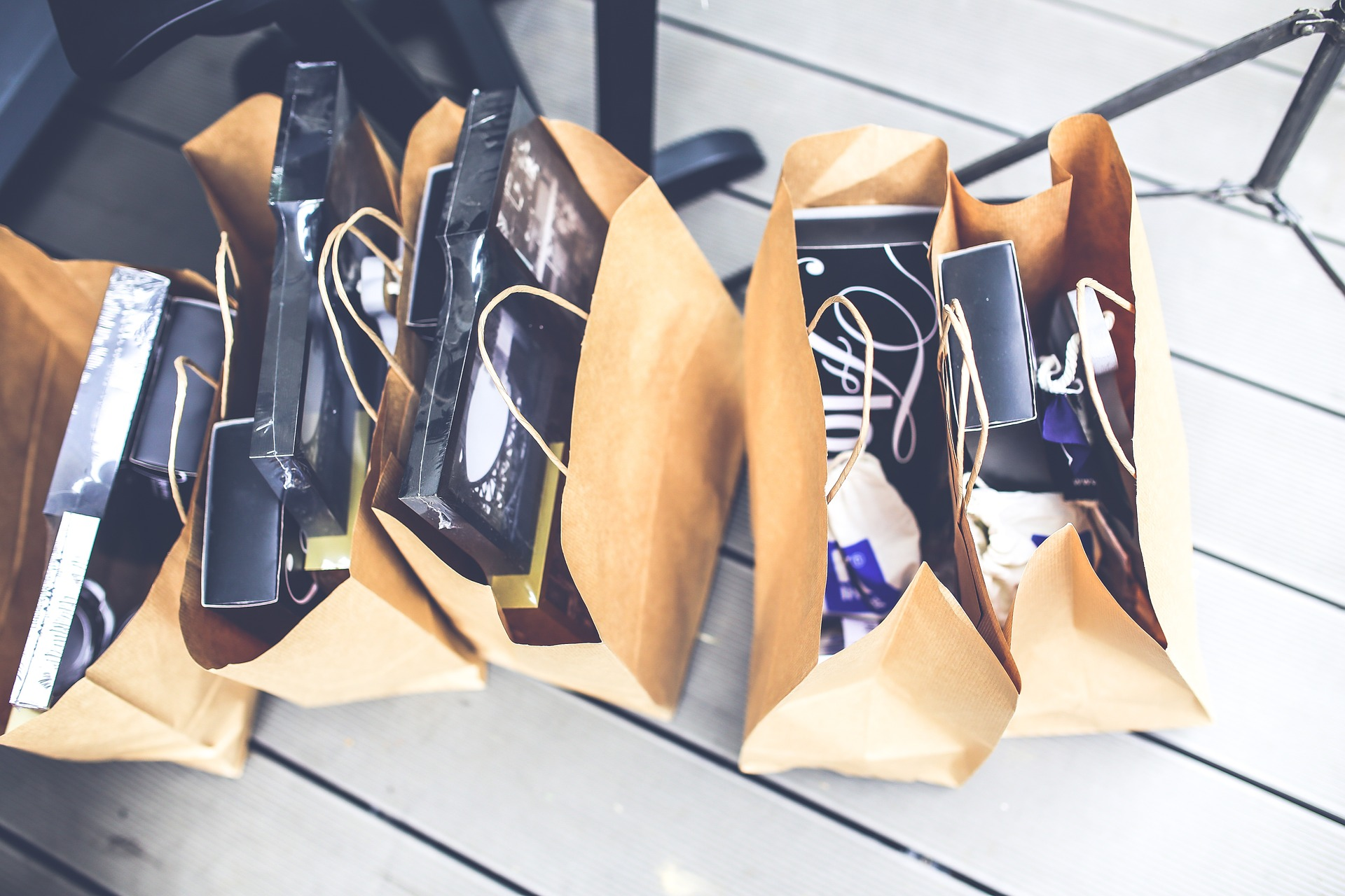 Five brown paper bags with items inside placed on the floor.