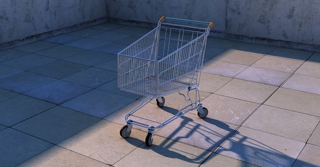 A grocery shopping cart placed outside under the sunlight.