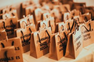 Bulk brown paper bags with handles and with brand names printed in front made by a paper bag supplier.