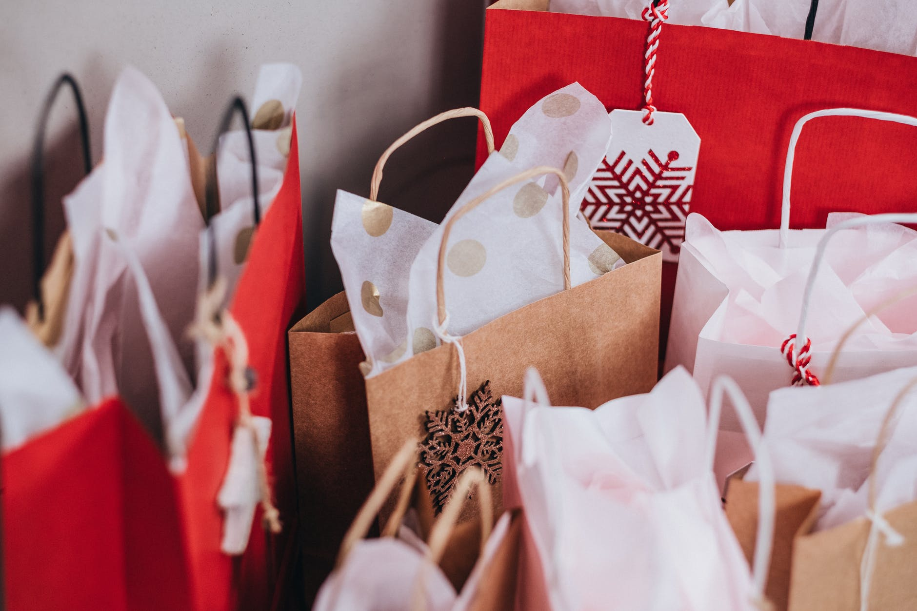 Brown and red paper bags with handles and with designs.