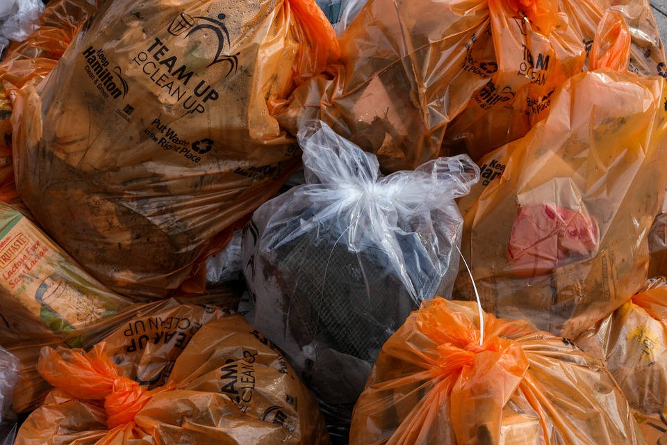 Plastic bags that are tightly closed with different types of garbage inside piled in one place.