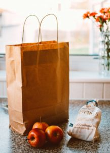 brown bag with handle, apples and bread bag on the table