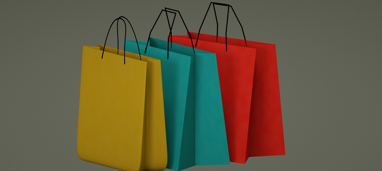 three different colored shopping bags side by side
